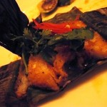 Grilled white fillet of fish with lemongrass wrapped in banana leaves